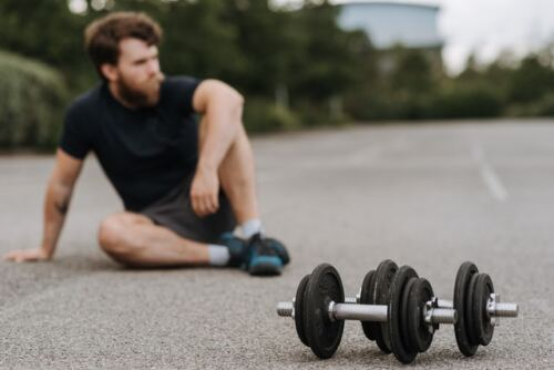 Here's How and If 30-Day Fitness Challenges Really Work, tired man sitting on the floord with dumbbells in front of him (1)